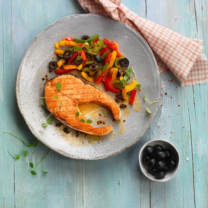 Rodaja de salmón con pimientos salteados y aceitunas negras