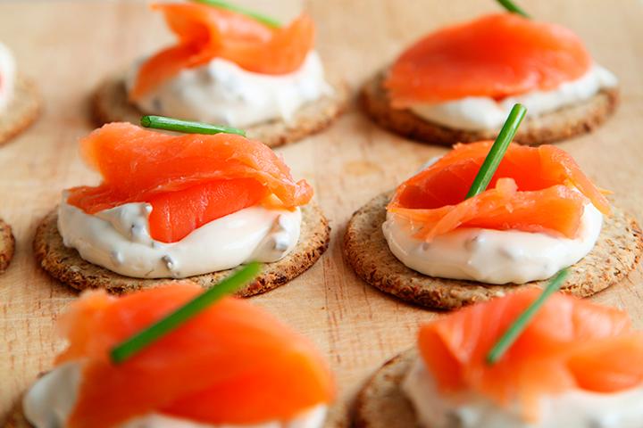 ¡Los snacks ligeros siempre triunfan! Puedes preparar platos tan sencillos como estas deliciosas tostadas con queso cremoso y salmón.